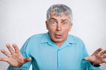 Scared matured wrinkled male expresses negative emotions, gestures and looks with unexpected expression into camera, wears formal shirt, isolated over white background. Facial expressions concept