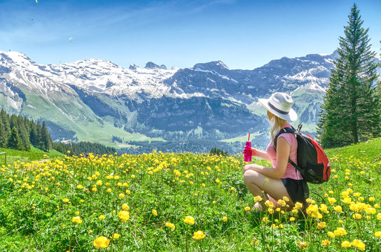 Swiss Alps. A girl sitting on the grass, drinking water from a bottle and admiring the mountain scenery. Engelberg Resort