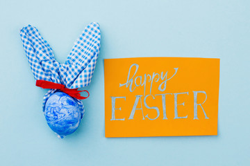 Easter greeting card on blue background. Handmade Easter bunny with red ribbon. Spring season holiday.