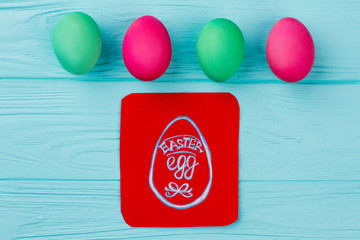 Close up Easter colorful eggs and picture. Image of Easter egg on red card. Christians symbols and tradition on Easter holidays.