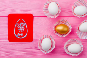 Easter festive composition with eggs. Red paper card with picture of Easter egg. Gold egg and white eggs. Spring holidays background.