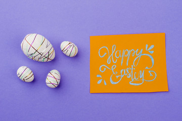 Happy Easter card and decorative eggs. Four styrofoam festive eggs and Easter greeting card on purple background.