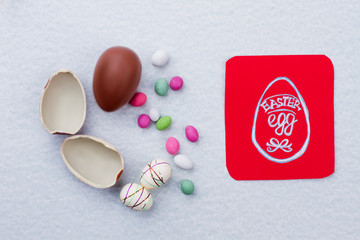 Easter background with sweets and eggs. Red paper card with picture of Easter egg. Easter greeting ideas for kids.