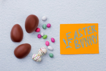 Candies and eggs on light blue background. Chocolate eggs and styrofoam Easter eggs. Card with text Easter bunny.