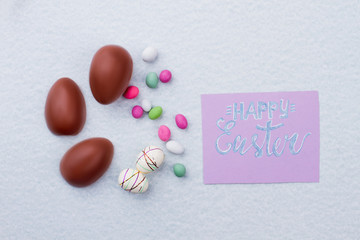 Happy Easter composition with chocolate eggs. Sweets and festive polystyrene eggs on light background. Spring season holiday.