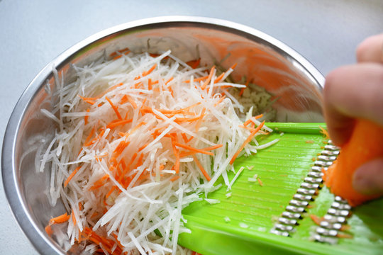 Hand grating carrot into stainless steel bowl