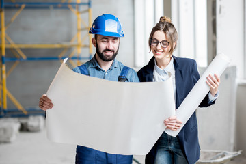 Foreman expertising the structure with businesswoman holding a blueprints at the construction site indoors