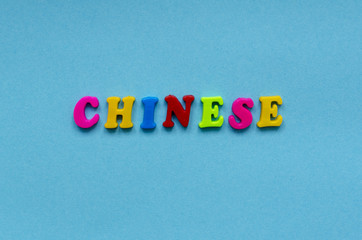 """word """"chinese"""" of colored plastic magnetic letters on blue paper background"""