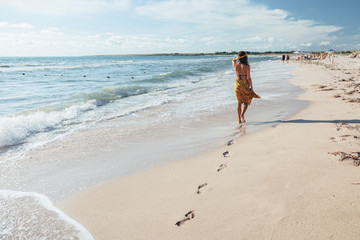 Boho girl walking on the beach