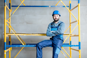 Builder in blue working uniform sitting on the scaffolding indoors