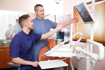 Two doctors in blue uniform in a dentist's office.