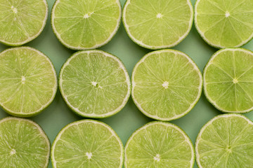 Limes split in half close-up on green background