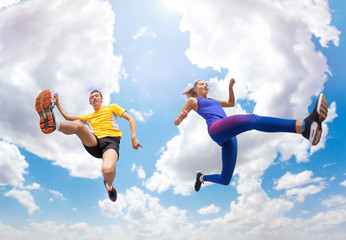 Athletes remains in air while jumping against sky