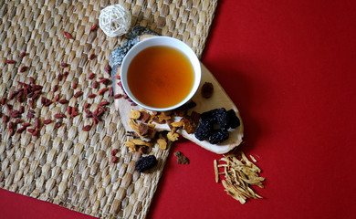 Goji berries, chinese dates, astragalus root pieces with a bowl of herb tea on red background. Top view.