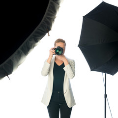 Woman photographer taking images in photographic studio with dslr camera on white background.
