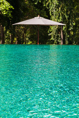 A white umbrella next to clear water in swimming pool
