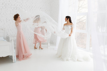 Cute girls celebrating a bride's bachelorette party and playing with veil in bedroom
