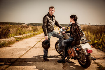 Wall Mural - Bikers couple Man and woman near a motorcycle on the road
