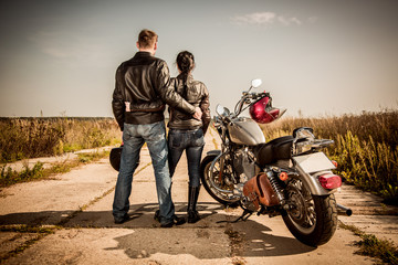 Wall Mural - Biker man and girl stands on the road and looks into the distance