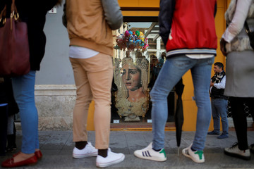 """People stand next to a picture of the Virgin as they watch the """"Lagrimas and Favores"""" brotherhood, during a Palm Sunday procession in Malaga"""