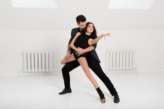 beautiful couple dancing bachata on white background in studio