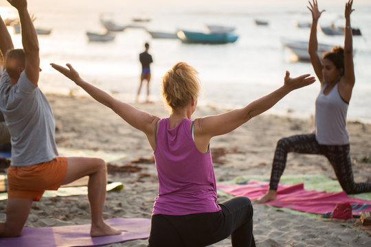Women doing yoga exercises or supported pigeon pose on an empty beach of the Indian ocean in Mauritius