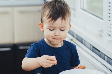 baby eating sausage in the kitchen is very charming and emotional
