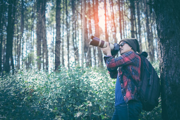 Man Traveler with photo camera and backpack hiking outdoor Travel Lifestyle and Adventure concept.