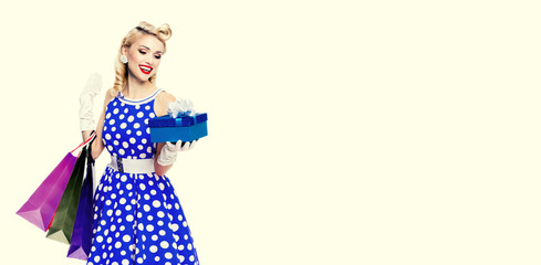 woman in pin-up style holding gift box and shopping bags