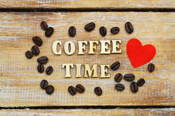 Coffee time written with wooden letters on rustic surface, red heart and coffee beans