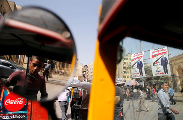 Posters of Egypt's President Abdel Fattah al-Sisi are seen from the broken glass of a car during preparations for the presidential election in Cairo