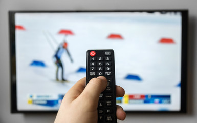 Male hand holding TV remote control. Biathlon.