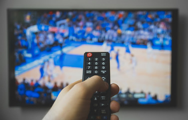 Male hand holding TV remote control. Basketball match.