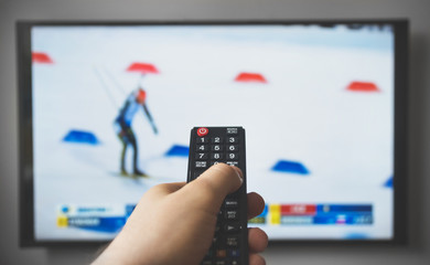 Male hand holding TV remote control. Biathlon.