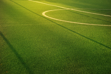 center of green football or soccer field for match or tournament with white line and morning sun light background