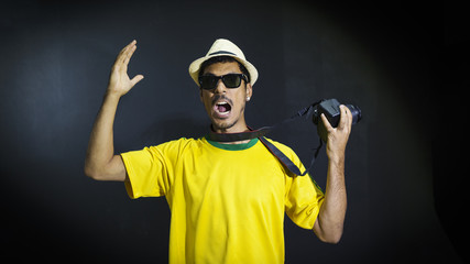 Tourist or fan in yellow uniform celebrating on black background