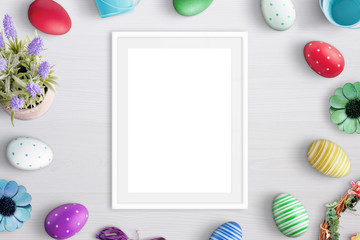 Blank picture frame surrounded with easter eggs and flowers.