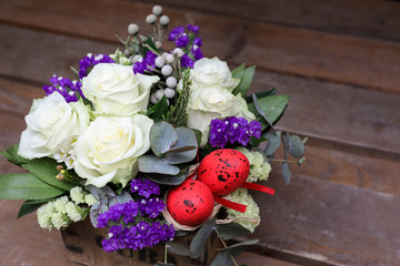 Festive flower arrangement of white roses, white and blue kermek and other plants, red eggs for Easter decorated.