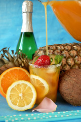 Glass with ice is being filled up with an orange drink surrounded by fruits. Champagne bottle in the background