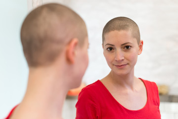 Young adult female cancer patient looking in the mirror, smiling, happy about her new short hair.