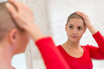 Young adult female cancer patient looking in the mirror, stroking her new short hair.
