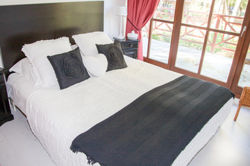 white and grey bedroom with large bed front of windows