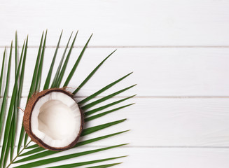 Half of coconut and palm leaf on the white wooden table