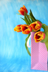 Red tulips in a present bag on blue background
