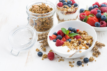 healthy breakfast with natural yogurt, muesli and berries on white wooden background, closeup