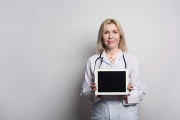 Doctor holding tablet computer with blank screen