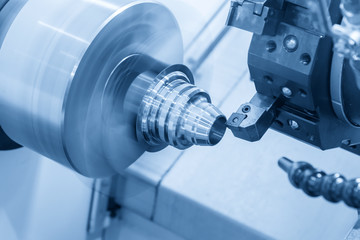The CNC lathe machine cutting the metal cone shape part in the light blue scene.