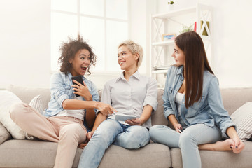 Three female friends using smartphones at home