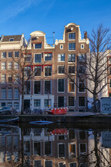 water canals in Amsterdam with traditional architecture reflecting in water on a sunny day