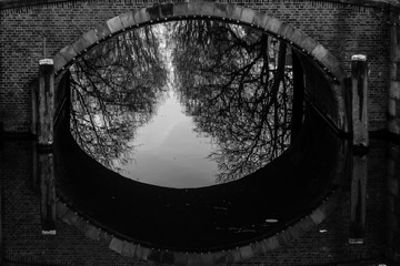 water canals in Amsterdam with a bridge in the middle and traditional architecture black and white